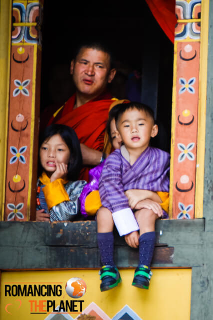 A father watching the Thimphu Domchoe along with his kids
