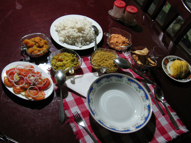 Rice served along with three vegetable curries, coconut sambol, salad, papadam and pineapple. Photo Source