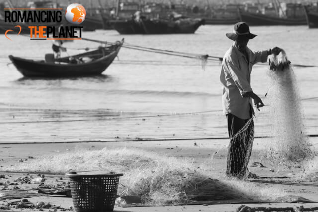 Fisherman collecting oysters from his fishing nets in Mui Ne, Vietnam