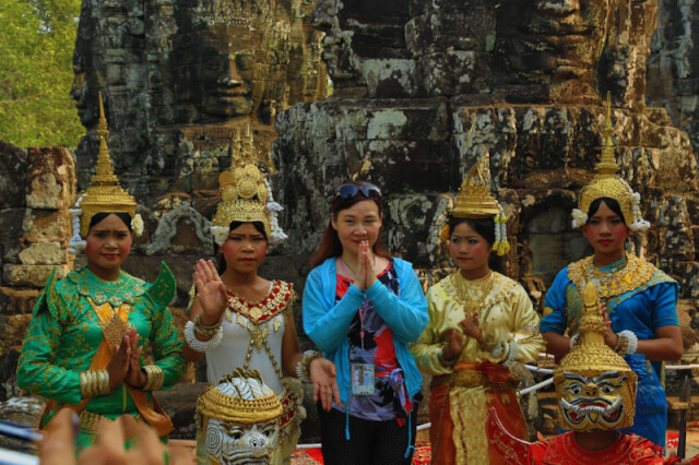 A woman posing with the Apsara in Bayon temple