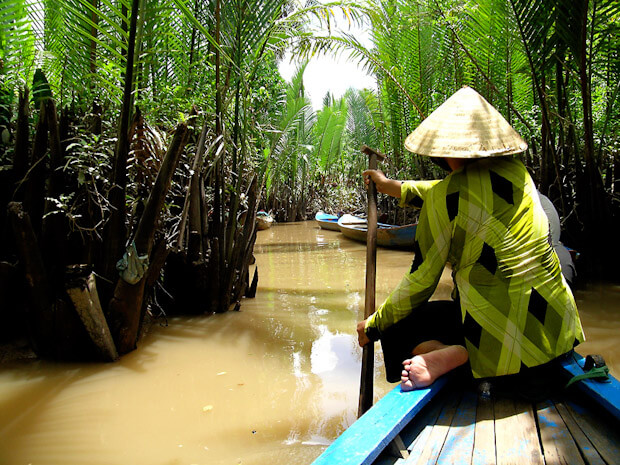 Vietnamese boatwoman, small river with palm trees, Mekong Delta