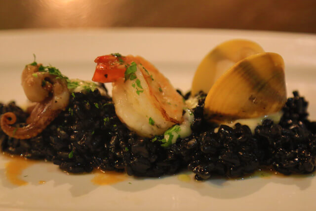 Rice cooked in Squid Ink accompanied with scallop, octopus arm and clam